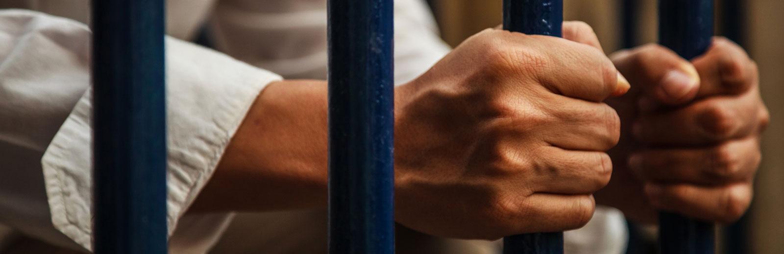 man in jail behind bars